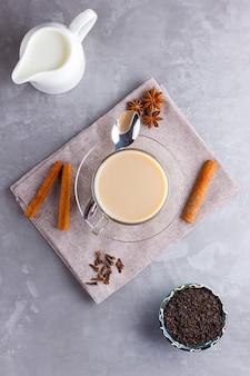 Masala chai tee. traditionelles indisches getränk - masala-tee mit gewürzen auf grauem hintergrund.