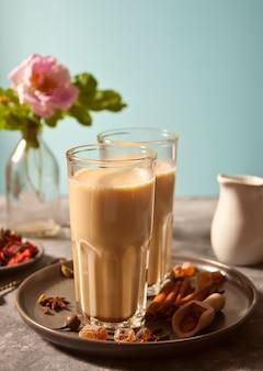 Masala tee chai mit milch und gewürzen.