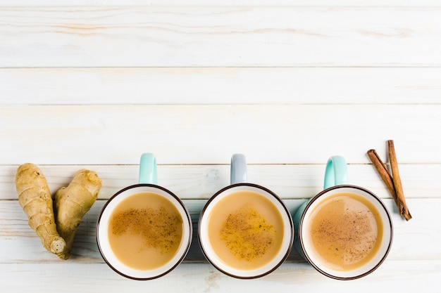 Masala-tee in keramikbechern mit den wintergewürzen zimt und ingwer