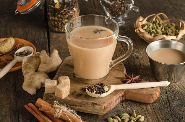 Masala-tee mit gewürzen auf einem hölzernen hintergrund, ein wärmendes getränk aus indien