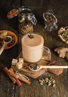 Masala-tee mit gewürzen auf einer holzoberfläche, ein wärmendes getränk aus indien