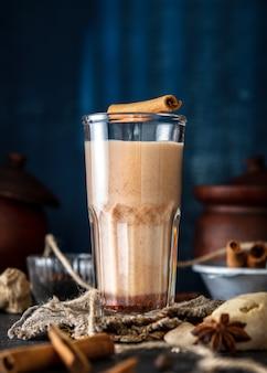 Masala-tee mit zimt und anis auf blauem grund. ein glas masala-tee mit gewürzen auf einem betontisch.
