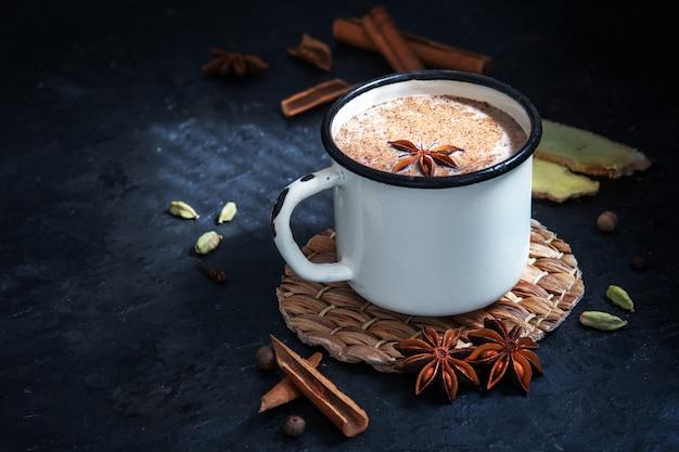Masala-tee mit zimt und anis auf einem blauen betontisch. eine weiße tasse masala-tee mit gewürzen auf einem betontisch.