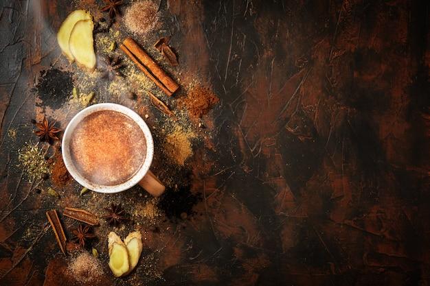 Masala-tee mit zimt und anis auf einem tontisch. eine tasse masala-tee mit gewürzen auf einem konkreten hintergrund. draufsicht.