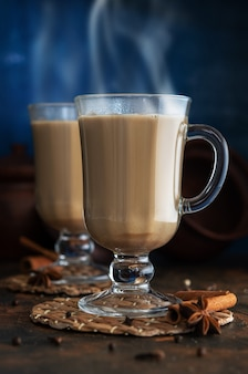 Masala-tee mit zimt und badian auf einem tontisch. zwei gläser tee masala auf einem blauen hintergrund.