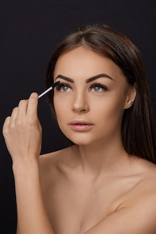 Mascara, beauty make-up, frische, weiche haut und lange, schwarze, dicke wimpern, die mascara mit einem kosmetikpinsel auftragen, wimpernverlängerung, künstliche wimpern,