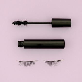Mascara und falsche wimpern auf lila hintergrund