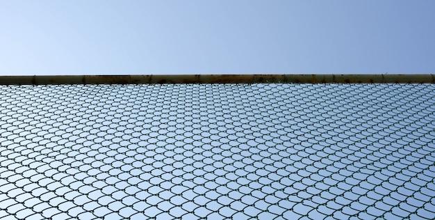 Maschendrahtstahl auf hintergrund des blauen himmels