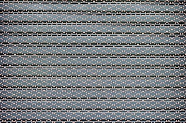 Maschendrahtzaun auf einem hintergrund von grauen stahltüren
