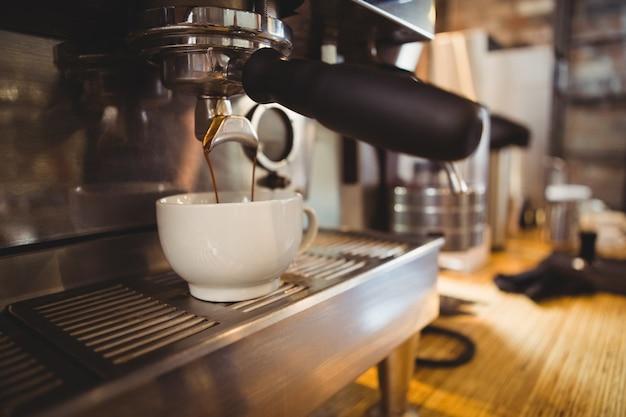 Maschine, die eine tasse kaffee in einem café macht