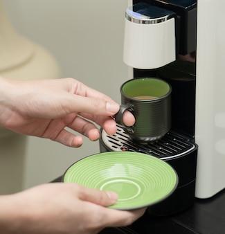 Maschine, die kaffee in einer tasse serviert. kaffeekapselmaschinenhersteller. hand, die eine keramische tasse kaffee auf der kaffeemaschine hält.