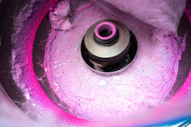 Maschine zum herstellen von zuckerwatte durch drehen und anstoßen des rosa zuckers.