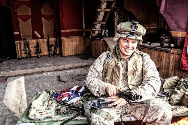 Maschinengewehrschütze des marine corps lächelt, zerlegt, macht wartung der dienstwaffe, überprüft den waffenlauf nach der reinigung am improvisierten außenposten in einem verlassenen gebäude