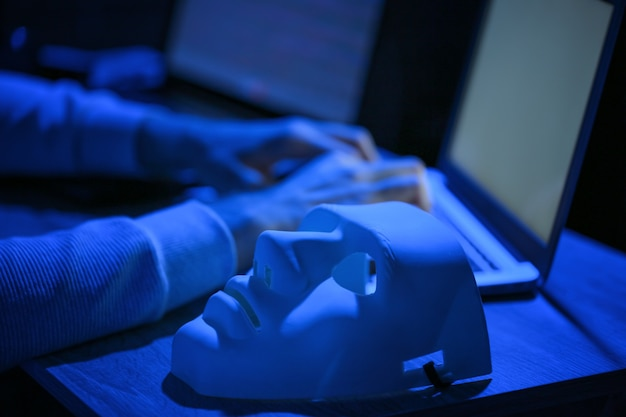 Maske auf dem tisch des professionellen hackers