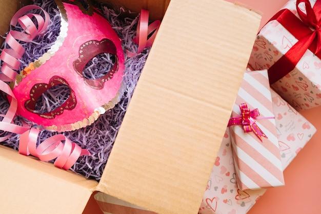 Maske in geschenkbox in der nähe von geschenken