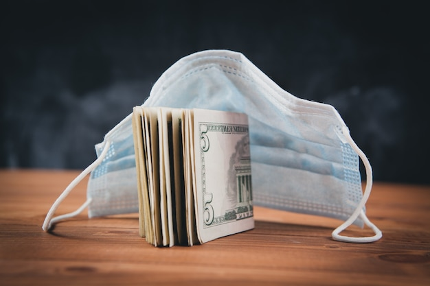Maske und dollarnoten auf dem tisch