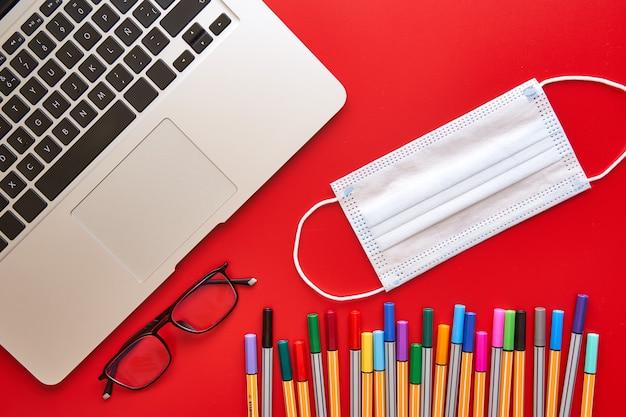 Maske und laptop auf dem schreibtisch