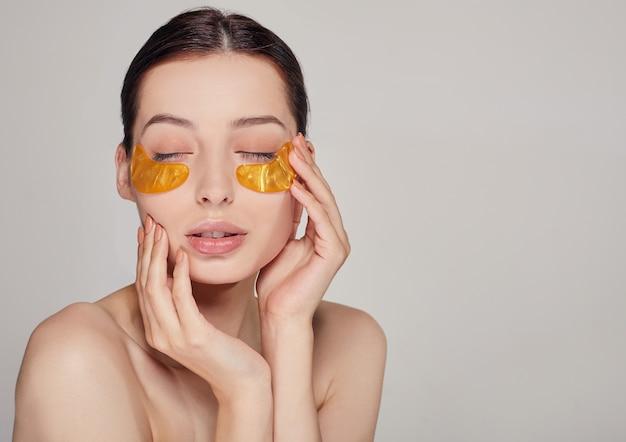 Maske zum entfernen von falten, augenringen. eine frau kümmert sich um empfindliche haut um ihre augen. kosmetische eingriffe.