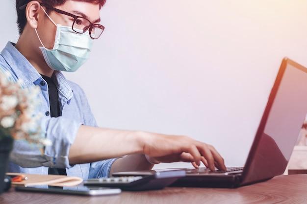 Maske zum schutzvirus, neue normale arbeit mit laptop im home office.
