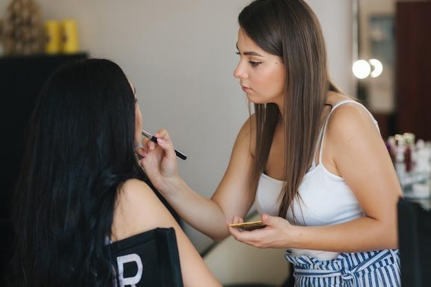 Maskenbildner arbeiten mit modell im schönheitsstudio