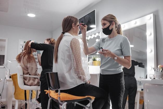 Maskenbildner bilden junge frauen im schönheitssalon. kundenservice im innenraum, um ein erstaunliches bild zu schaffen. assistent zur erstellung von arbeits-make-ups. konzept von stil und zufriedenheit messen. platz kopieren