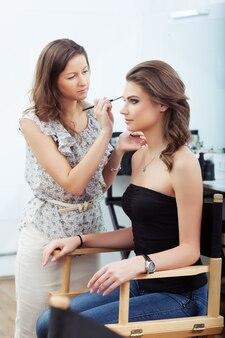 Maskenbildner, der augenbrauen-make-up aufträgt, selektiver fokus auf modell focus