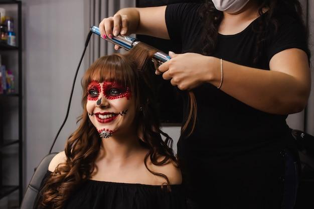 Maskenbildner, der das haar eines lächelnden mädchens mit dia de los muertos make-up kräuselt.