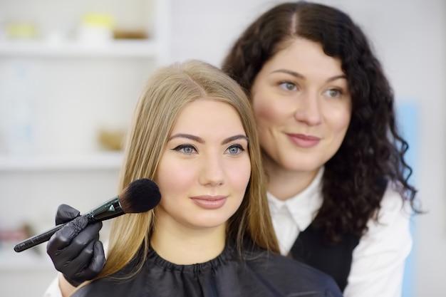 Maskenbildner, der den ton der grundierung mit speziellem pinsel auf gesicht junge schönes modell aufträgt. gesichtspflege und make-up
