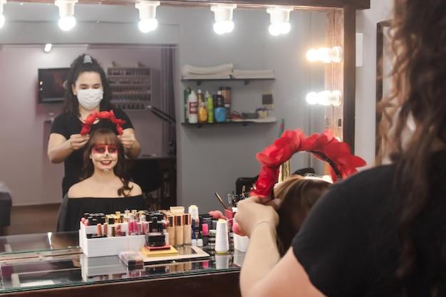 Maskenbildner, der einem schönen mädchen mit dia de los muertos make-up einen rosenkranz auf den kopf setzt.