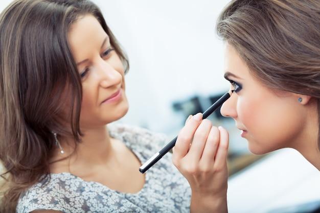 Maskenbildner, der eyeliner auf das unterlid des modells aufträgt