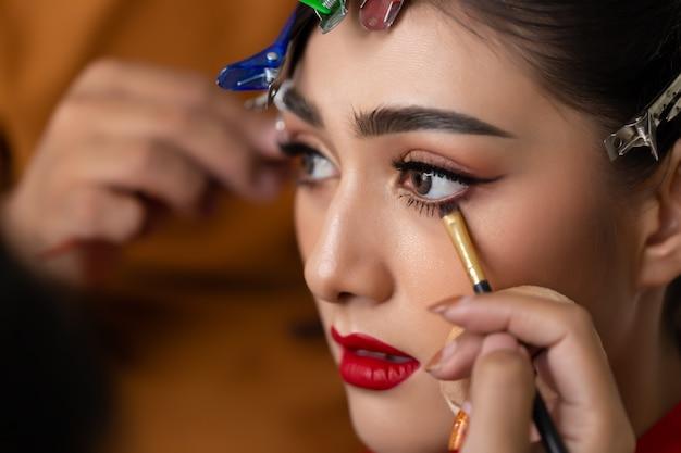 Maskenbildner, der eyeliner auf wasserlinie anwendet, indem er eyelinerpinsel verwendet