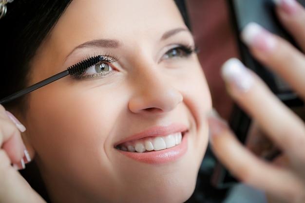 Maskenbildner, der flüssigen eyeliner mit bürste aufträgt