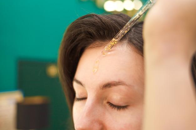 Maskenbildner, der kosmetisches öl auf gesicht der jungen frau aufträgt. make-up flüssige grundierung auftragen