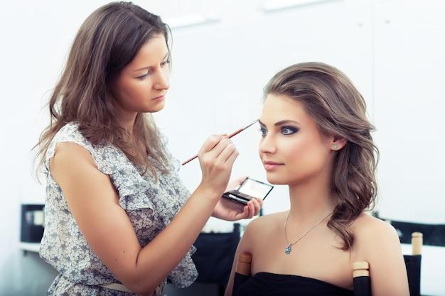Maskenbildner, der lidschatten-palette hält und augenbrauen-make-up aufträgt, selektiver fokus auf modell selective