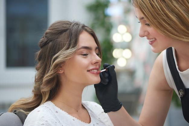 Maskenbildner, der lipgloss im schönheitssalon anwendet