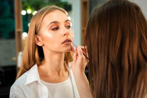 Maskenbildner, der lippenstift auf frau mit bürste anwendet
