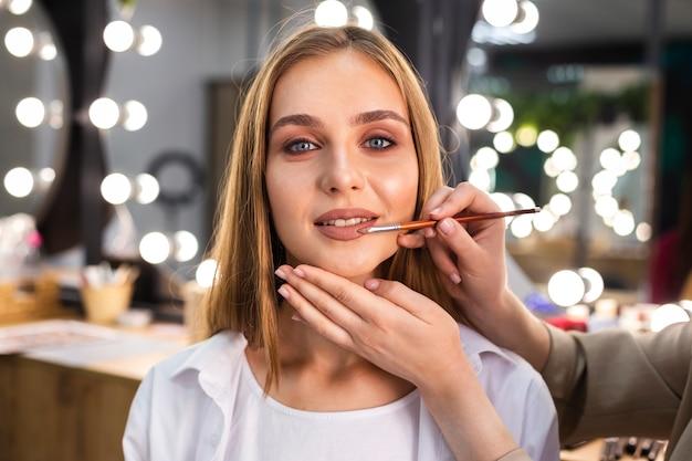 Maskenbildner, der lippenstift auf lächelnder frau mit bürste anwendet