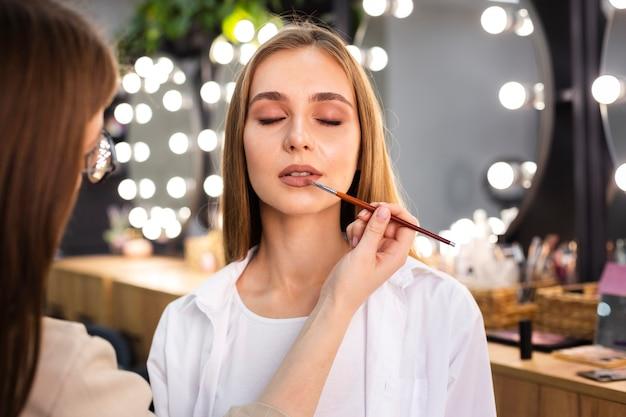 Maskenbildner, der lippenstift auf lippen unter verwendung des pinsels aufträgt
