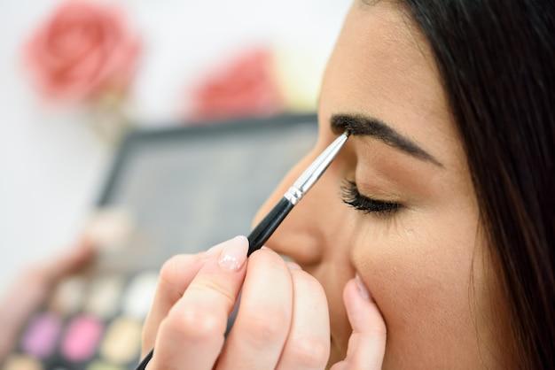Maskenbildner, der make-up auf die augenbrauen einer frau setzt