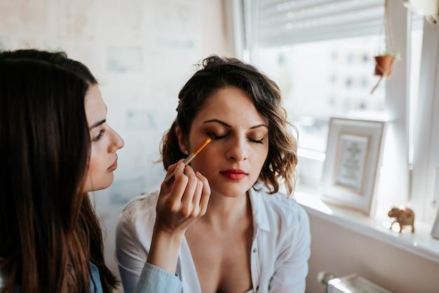 Maskenbildner, der make-up auf einem schönen mädchen anwendet. nahansicht.