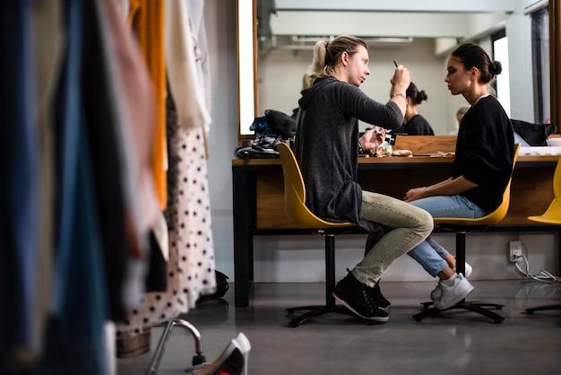 Maskenbildner, der make-up auf modell anwendet