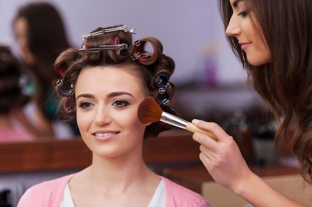 Maskenbildner, der make-up durch pinsel aufträgt