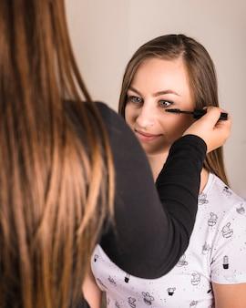 Maskenbildner, der make-up einer frau tut