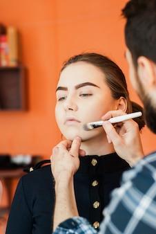Maskenbildner, der make-up eines schönen jungen mädchens im studio tut