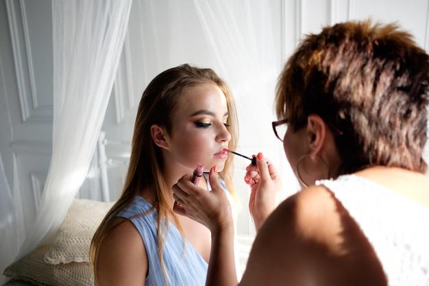 Maskenbildner, der make-up für junge hübsche brunettefrau macht