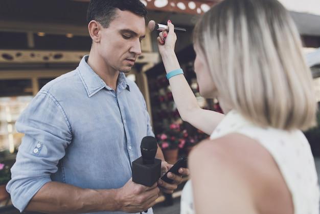Maskenbildner, der make-up tut, journalist, der im telefon schaut.