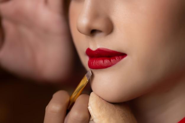 Maskenbildner, der roten lippenstift auf schönem vorbildlichem mund anwendet, indem er lippenbürste verwendet