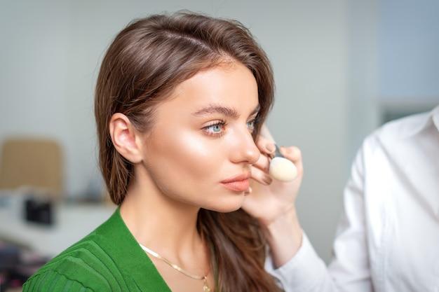 Maskenbildner, der trockene kosmetische tongrundierung auf dem gesicht der jungen frau unter verwendung des pinselwerkzeugs im schönheitssalon anwendet