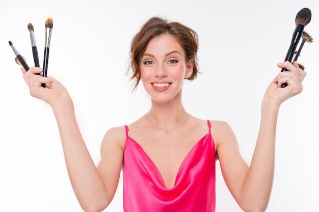 Maskenbildner in einem rosa kleid hält make-up-pinsel in zwei händen an einer weißen wand