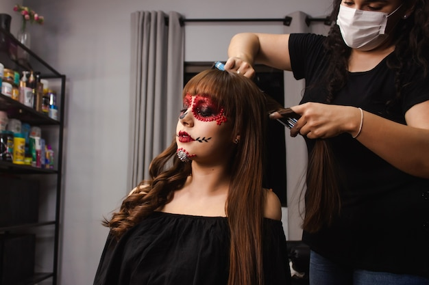 Maskenbildner kräuselt die haare eines jungen mädchens mit dia de los muertos make-up im schönheitssalon.